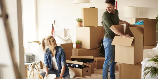 Couple with sorting boxes out after moving in