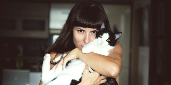 Woman cuddling a white and balck cat