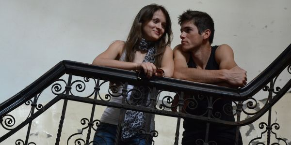 young couple leaning on stair rails looking at each other