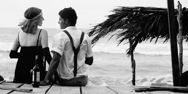 black and white shot of a couple by the beach