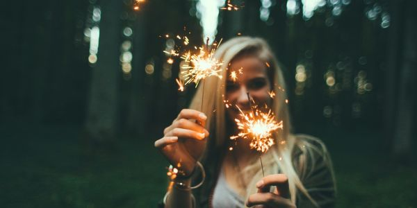 Blond girl holding sparkle candles on both hands